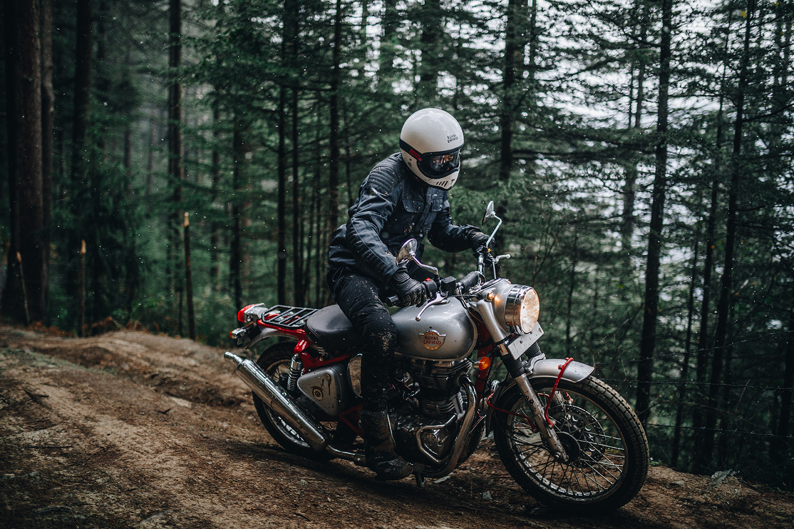 man riding the red royal enfield bullet 500 trials motorcycle in the forest